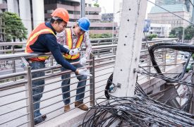 Electric_utilities_two_men_work_city_wires